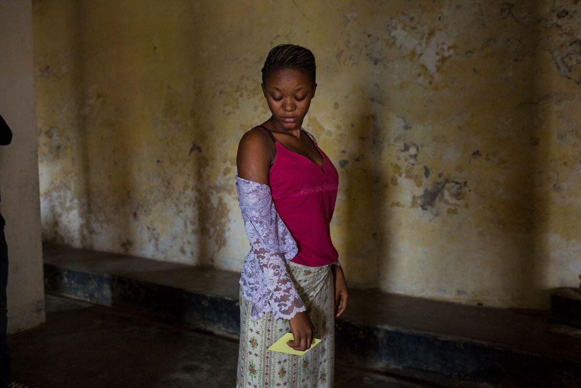 Acabada de ser vacinada contra a febre amarela, uma jovem congolesa aguarda que o seu braço ...