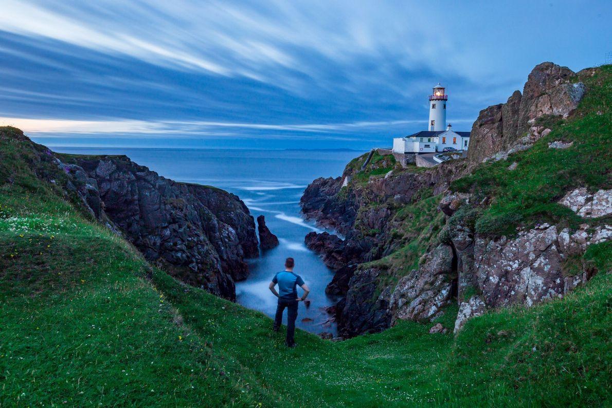Nuvens por cima de um mar azul enquadram o farol de Fanad Head, com 202 anos, ...