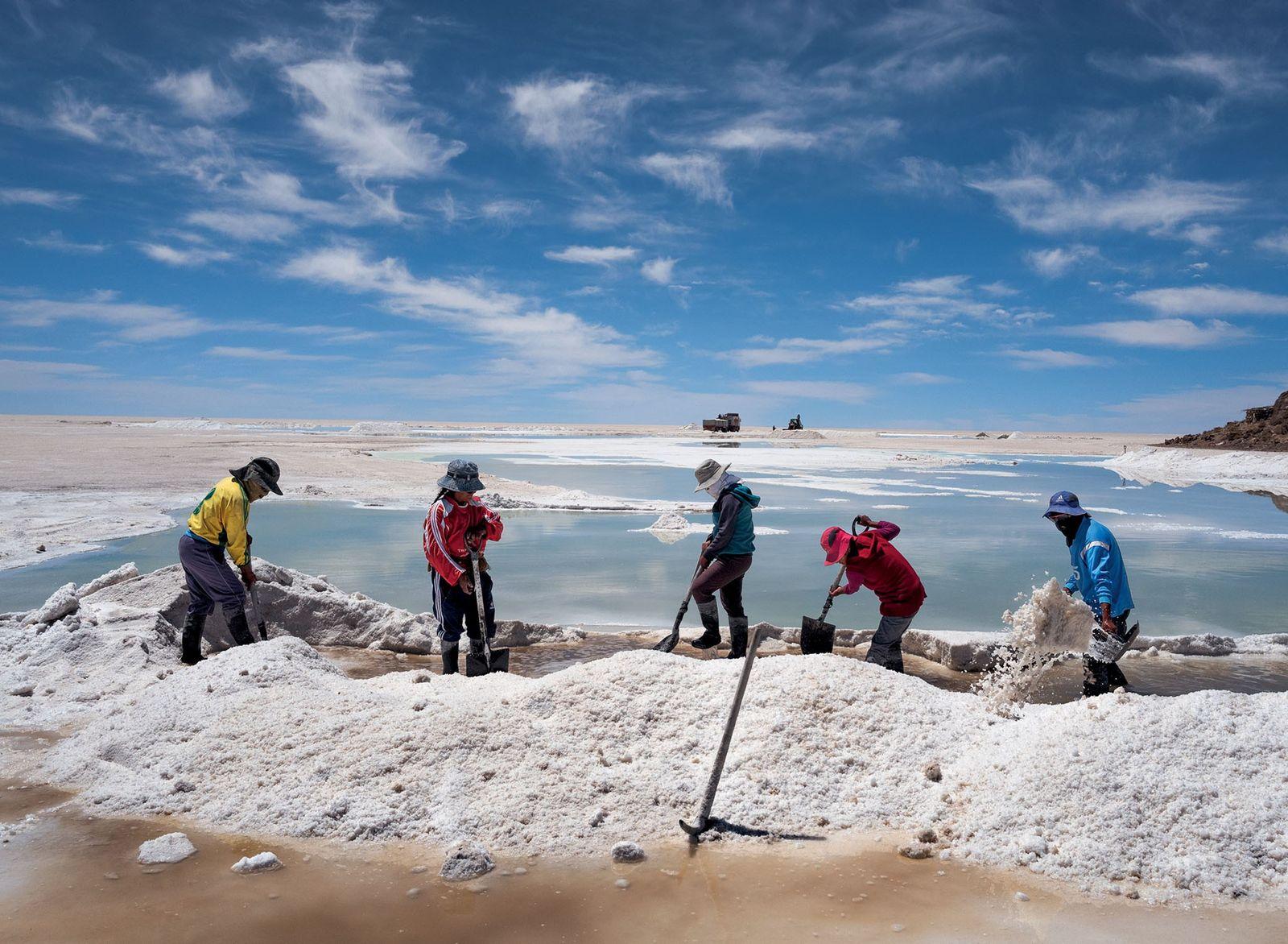 A população indígena Aimará colhe sal para vender na planície de sal de Uyuni, na Bolívia, ...