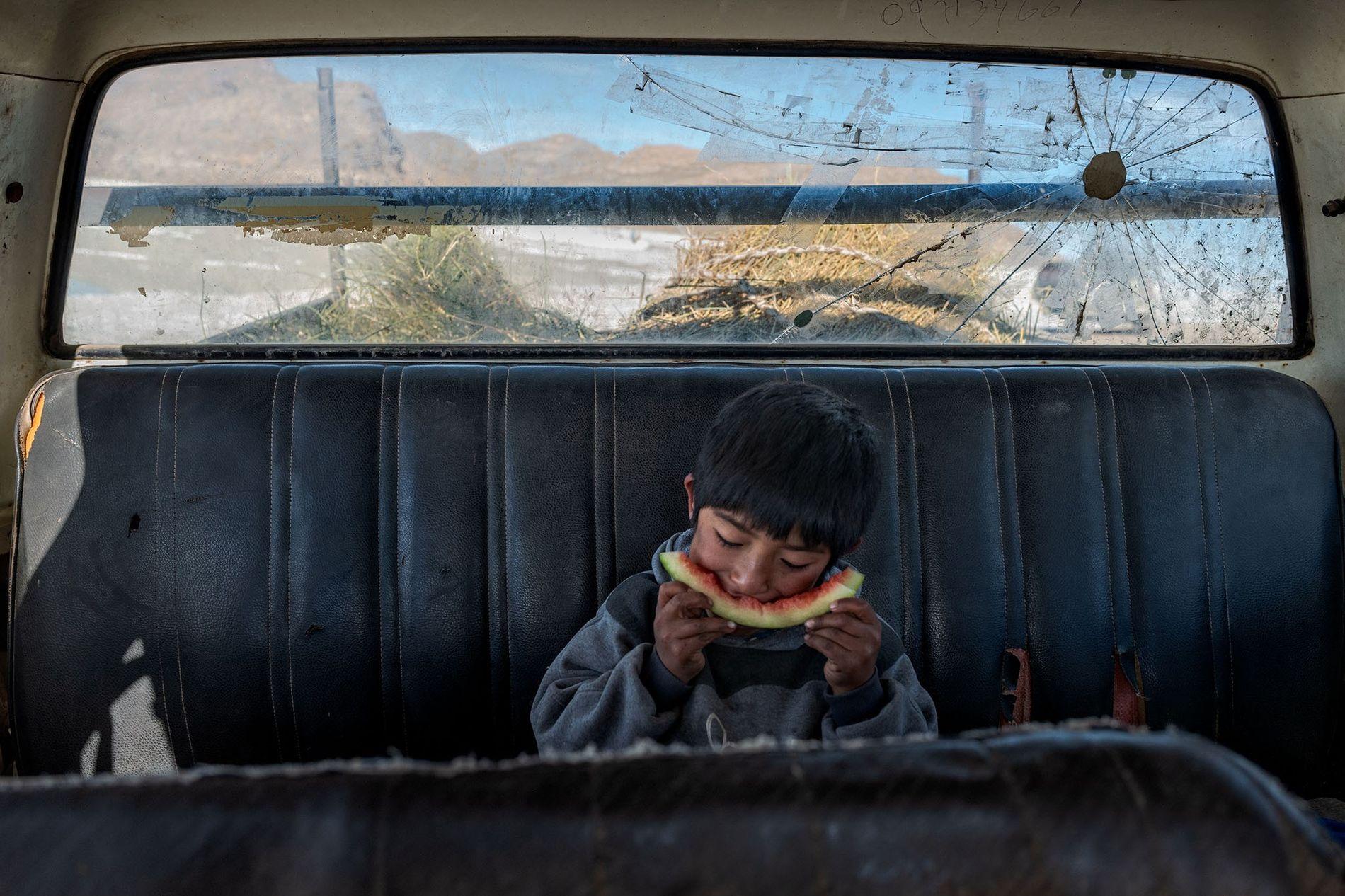 Angelo Martín Flores Chambi faz uma pausa para comer uma fatia de melancia, no carro da ...