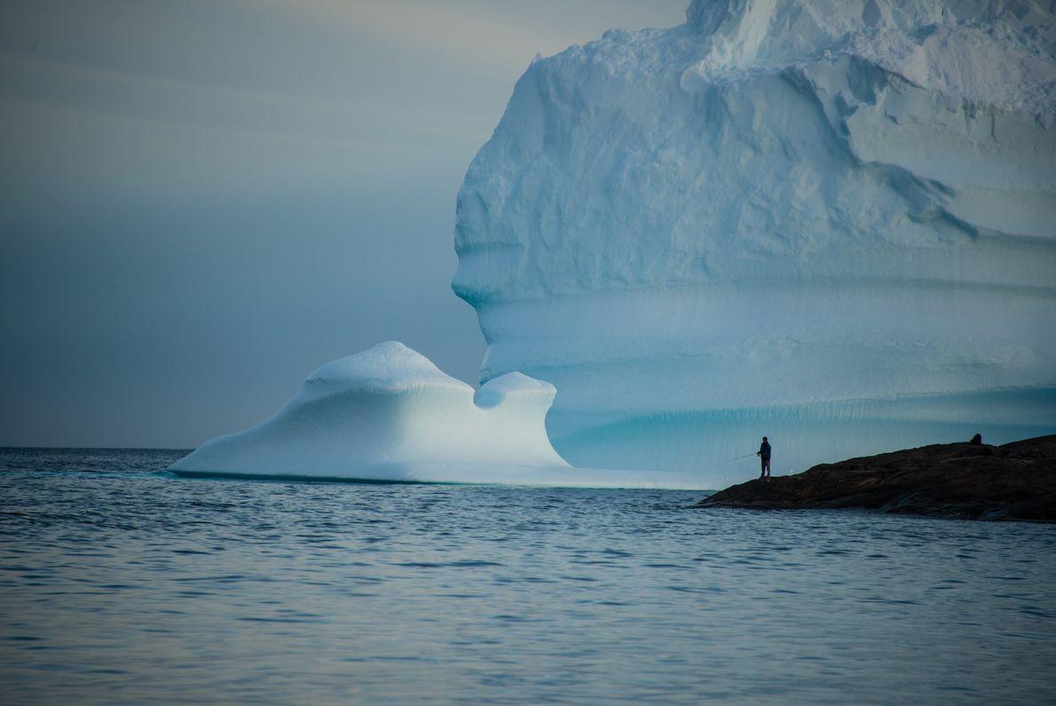 Um pescador lança a sua linha na costa sudeste da Gronelândia. Os rios e lagos da ...