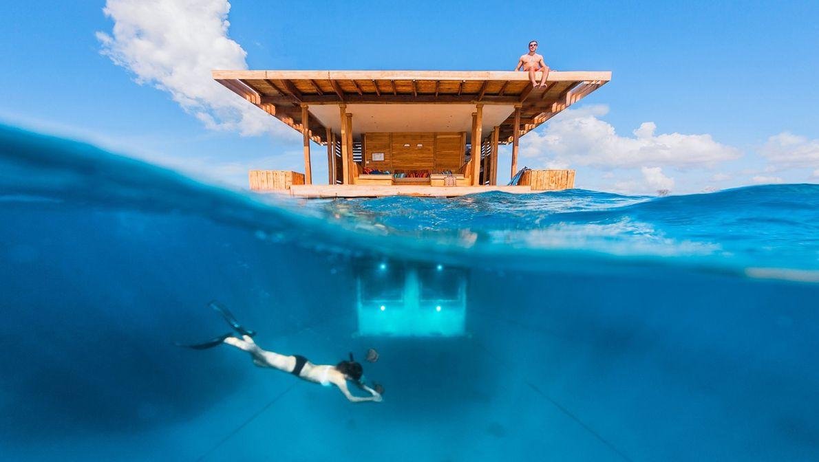 Um praticante de snorkeling mergulha nas águas azul-cobalto.