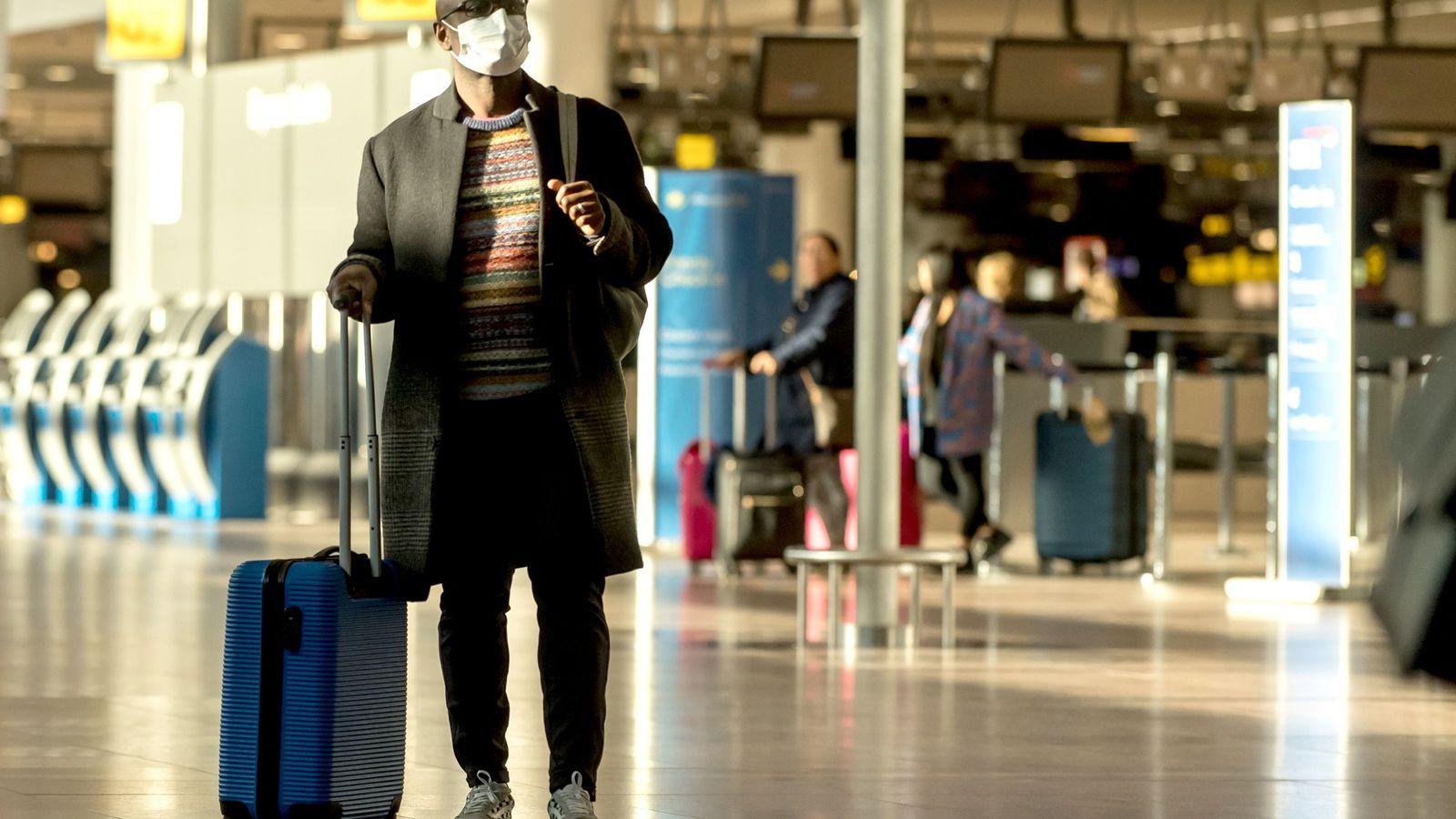 No aeroporto de Bruxelas, um homem usa uma máscara de proteção devido ao surto de coronavírus.
