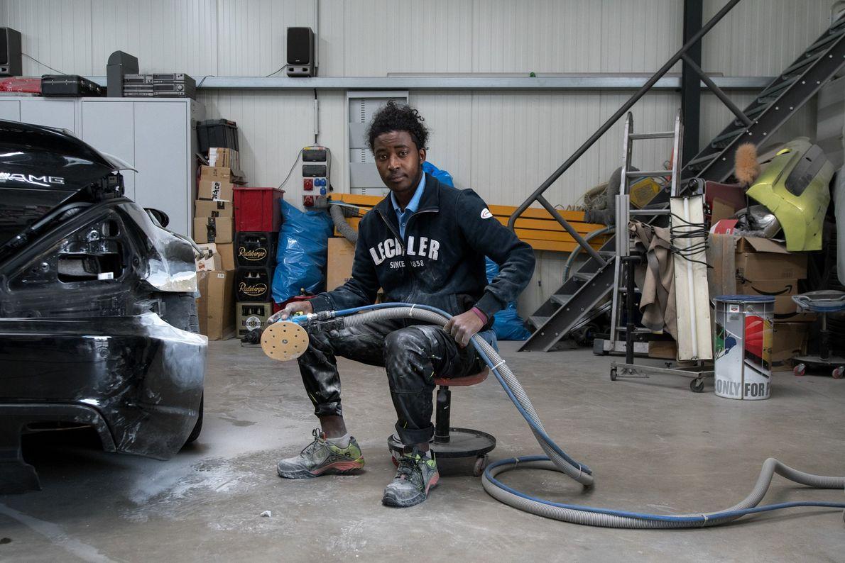 Atoy Eyob, migrante de 19 anos da Eritreia, usa uma lixadora para remover a tinta de ...