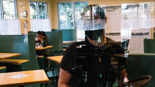 Uma cliente sentada e um empregado no Magnolia Pancake Haus em San Antonio, no Texas, na ...