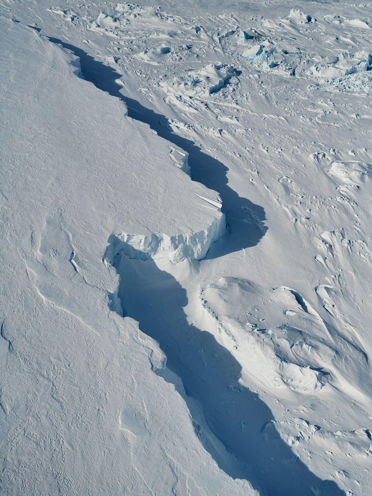 Sob a luz polar oblíqua, os enormes penhascos no limite do icebergue criam sombras profundas.