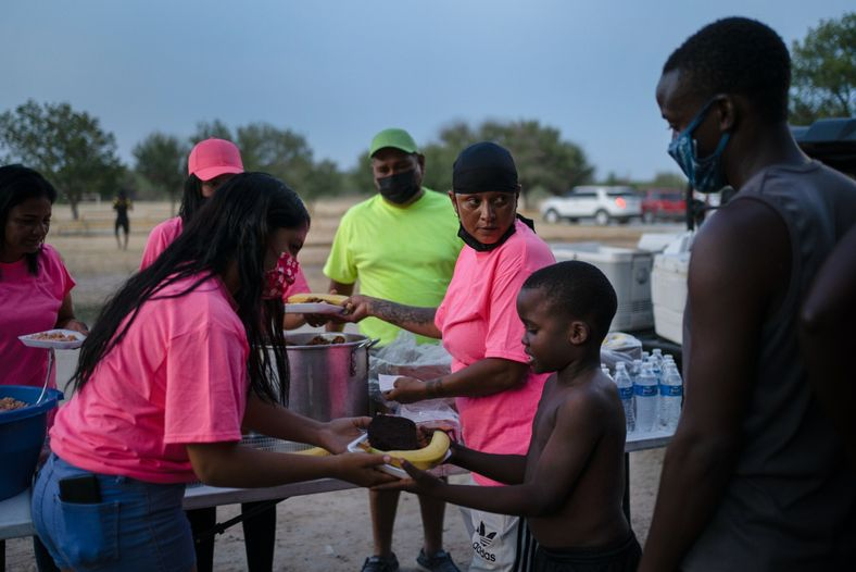 Um grupo de mulheres leva comida para os migrantes haitianos no dia 20 de setembro de ...