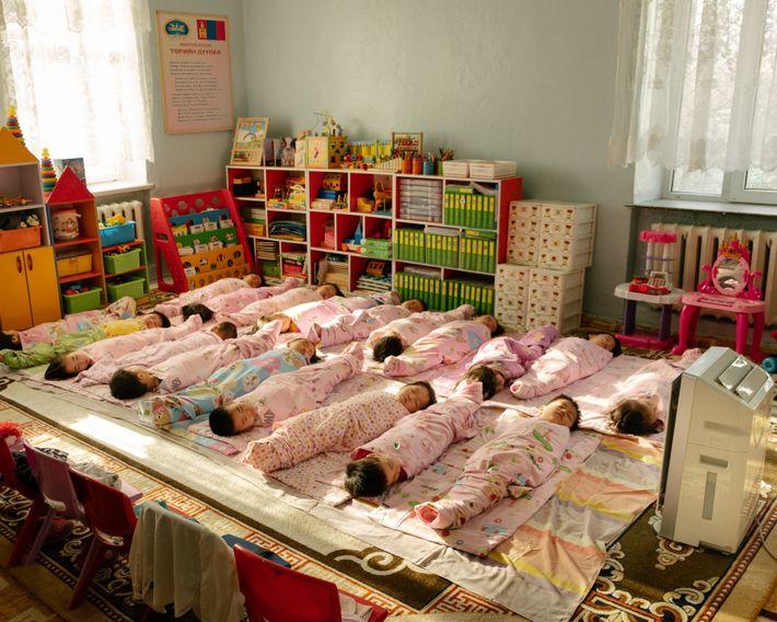 Crianças a dormir a sesta num jardim de infância, no distrito de Bayanzurkh, na Mongólia. Todos ...
