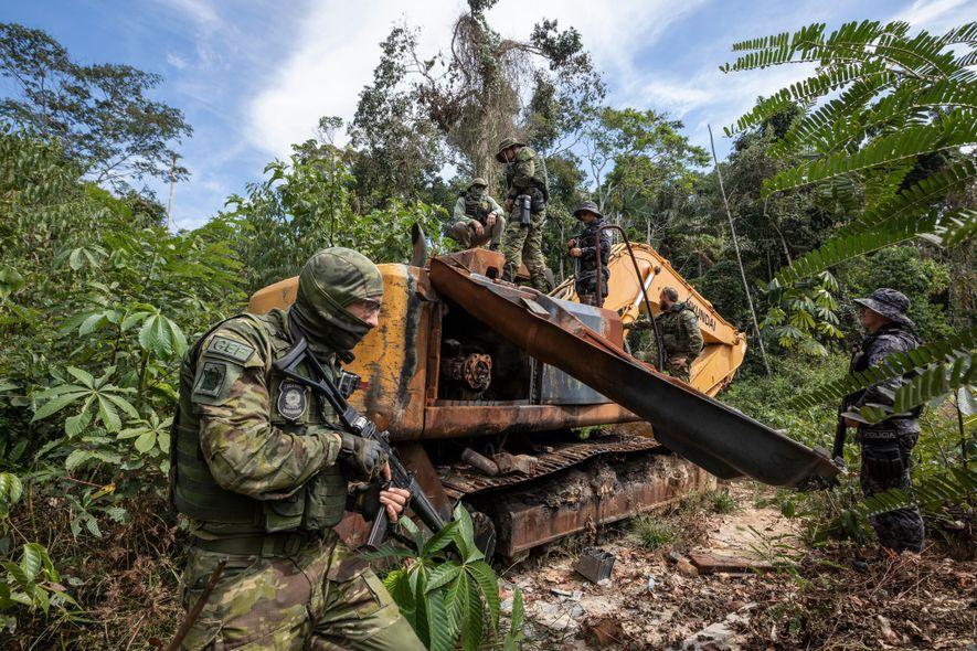Oficiais do Grupo de Inspeção Especial da agência brasileira de proteção ambiental, IBAMA, desmontam um trator ...