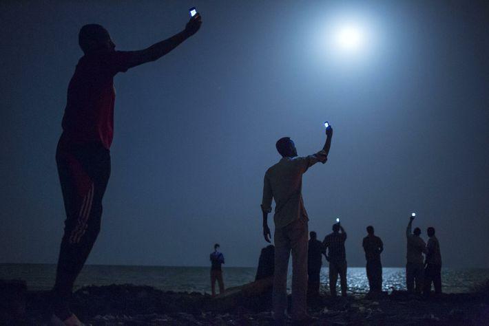 migrantes somalis em Djibouti tentam captar sinal de telemóvel