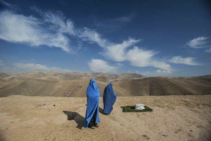 Duas mulheres aguardam na encosta de uma montanha no Afeganistão