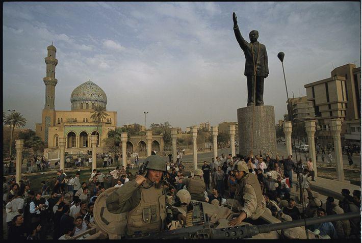 Fuzileiros dos EUA ajudam o povo iraquiano a derrubar uma estátua de Saddam Hussein