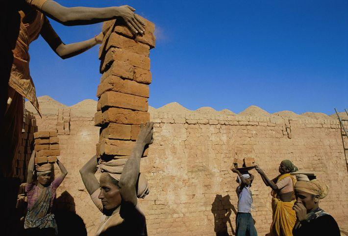 trabalhadores endividados que empilham e carregam tijolos na Índia