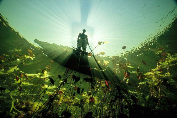 pescador perscruta as águas esmeralda do rio Okavango no Botswana