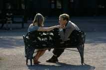 Um casal namora num banco de um parque.