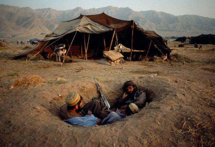 Combatentes afegãos tentam proteger-se durante o conflito de 2001. Os Estados Unidos invadiram o Afeganistão após ...