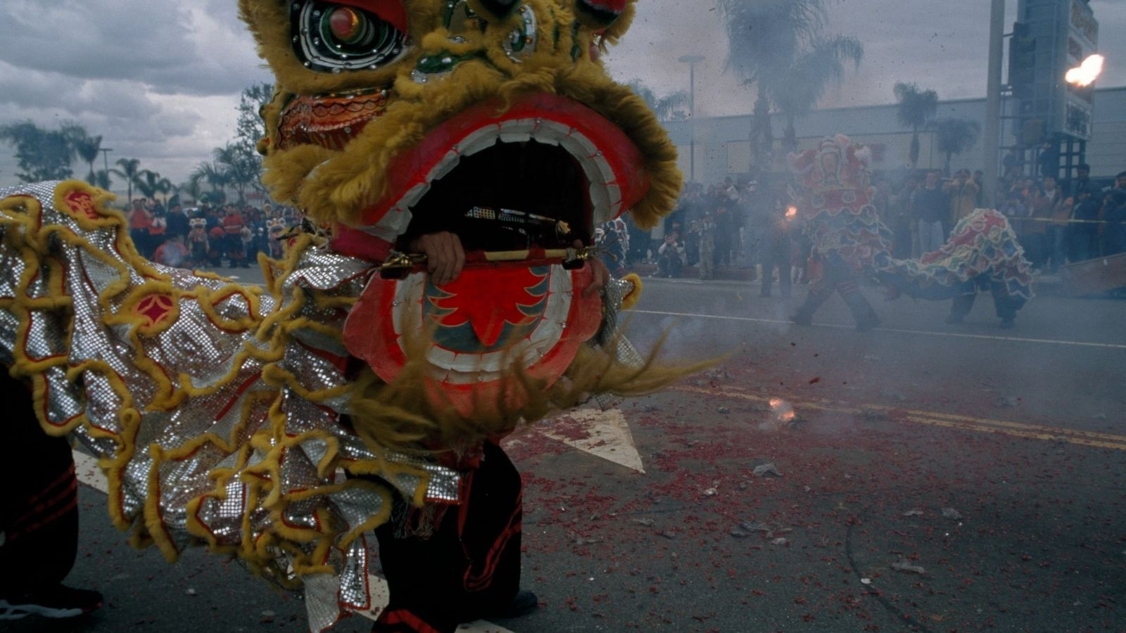 A fumaça de fogos de artifício e um dragão a dançar durante o festival de ano ...