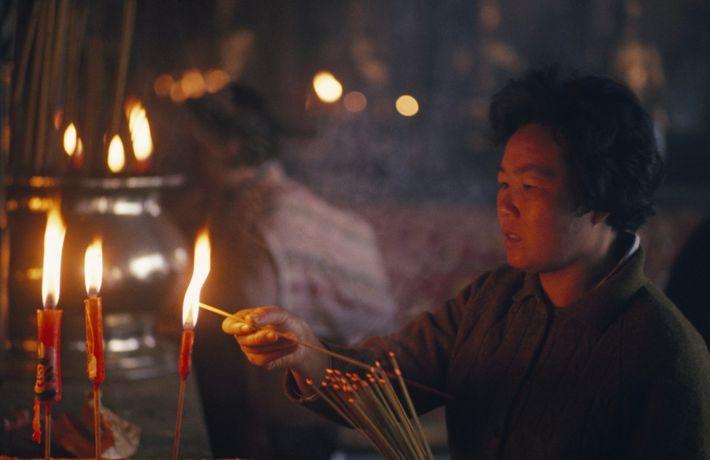 Budista acende um bastão de incenso enquanto profere orações num templo.