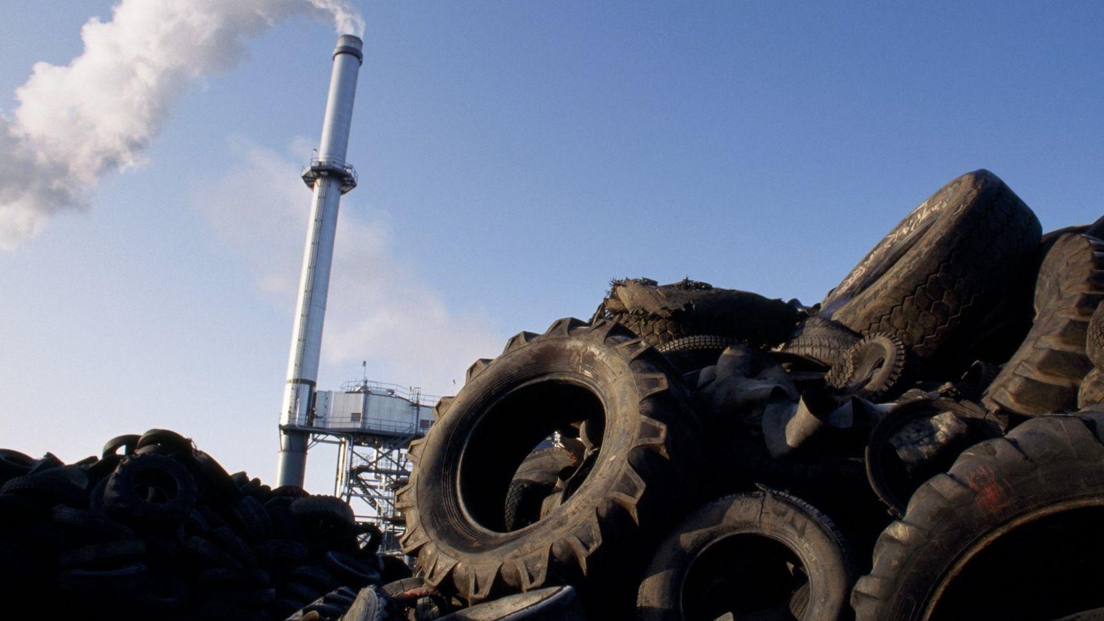 Os pneus velhos são empilhados perto da chaminé da Oxford Energy Company, que os utiliza para ...