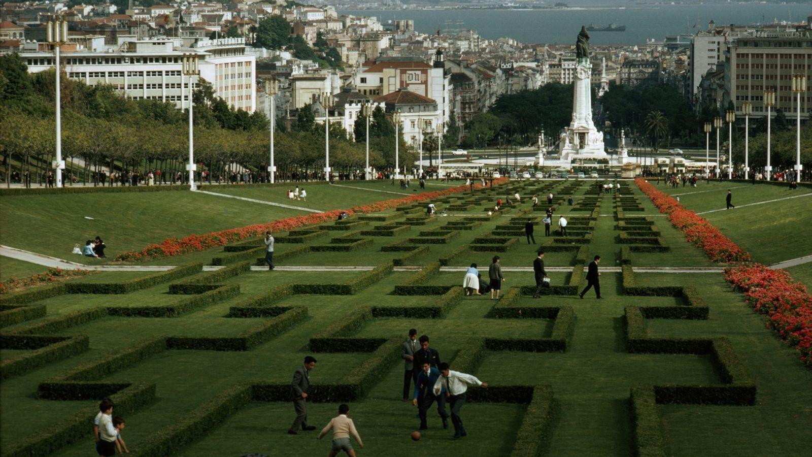 Pessoas passeiam e jogam futebol no jardim esculpido, com a estátua do Marquês de Pombal nas ...
