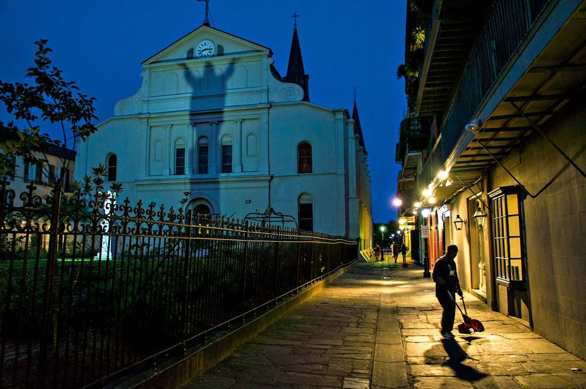 As luzes da rua iluminam um homem a varrer, enquanto o crepúsculo se instala sobre a ...