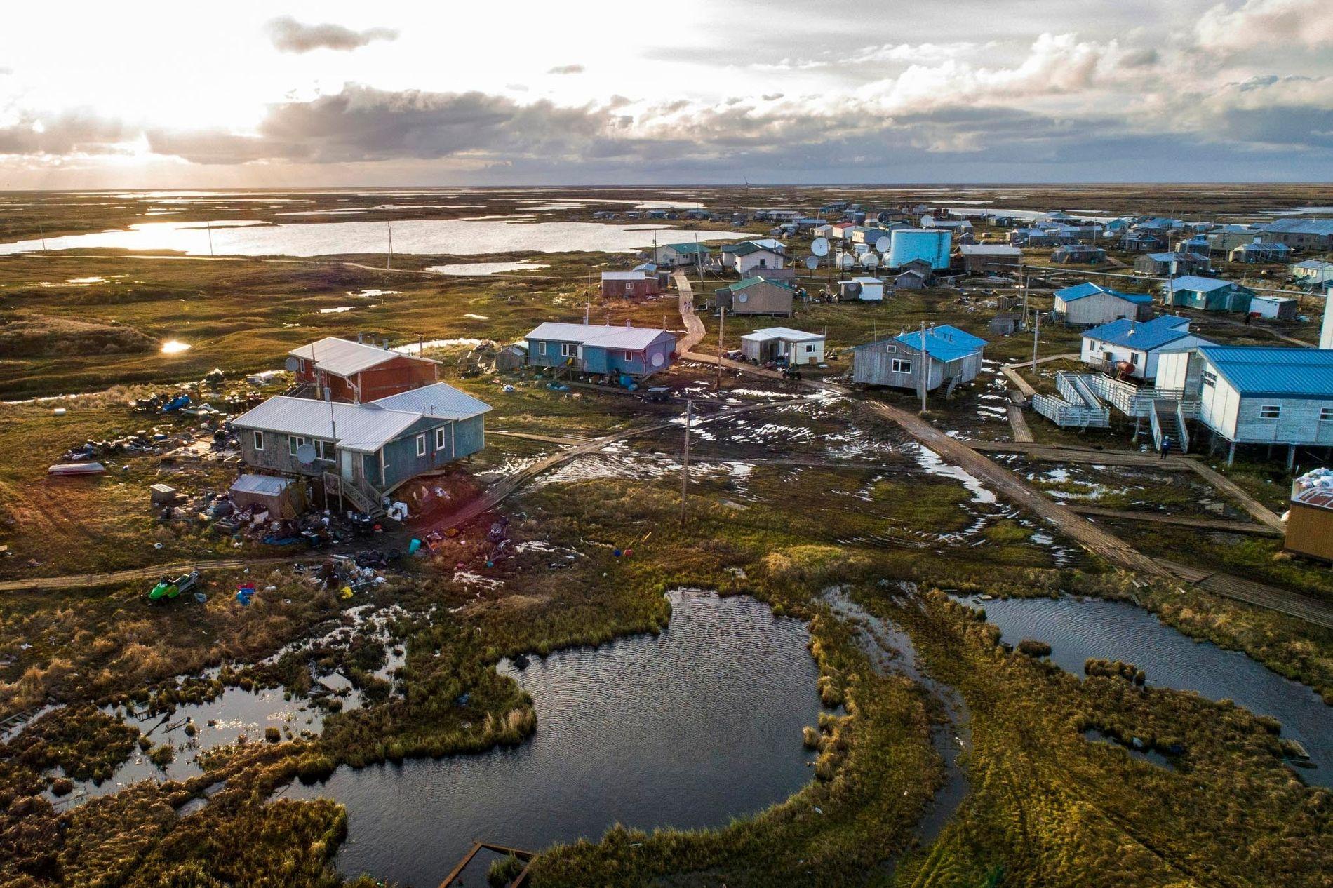A aldeia de Newtok, no Alasca, é ladeada pelos rios Ninglik e Newtok. A aldeia, nesta imagem, está a afundar-se rapidamente devido ao clima quente, ao degelo do pergelissolo e à erosão. Newtok é a primeira comunidade do Alasca forçada a mudar-se devido aos efeitos das alterações climáticas – tornando-se pioneira num processo que muitas outras vilas e aldeias do Alasca poderão em breve ser forçadas a seguir.