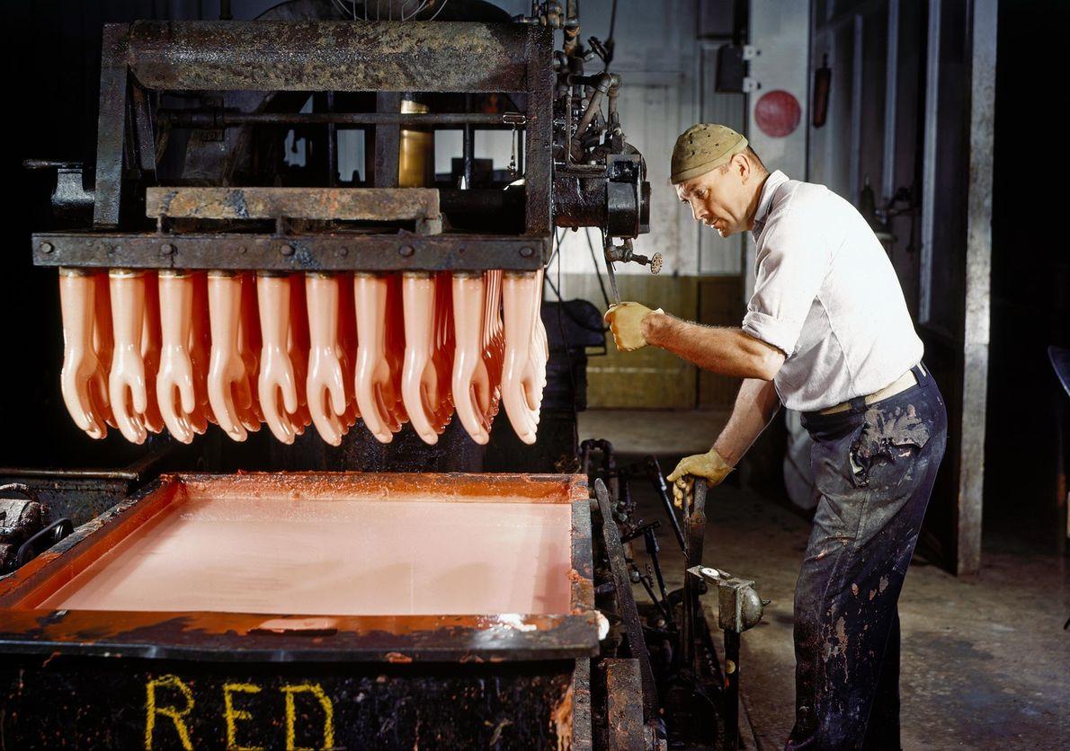 Um operário a produzir luvas de borracha a partir de um composto de borracha líquida. A ...