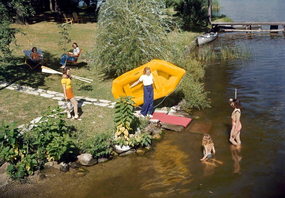 Uma jovem carrega um barco insuflável de borracha para um lago. Atualmente, as borrachas sintéticas ainda ...