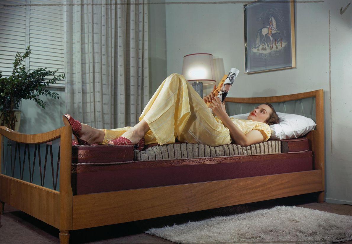 Uma mulher a ler numa cama que expõe o interior do colchão de borracha. Assim que ...