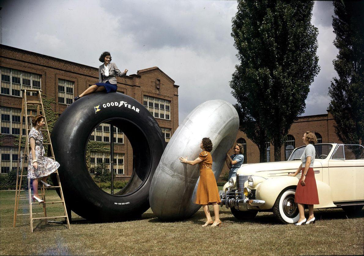 Mulheres posam com enormes pneus de borracha, construídos para um cruzador de neve gigantesco, para a ...