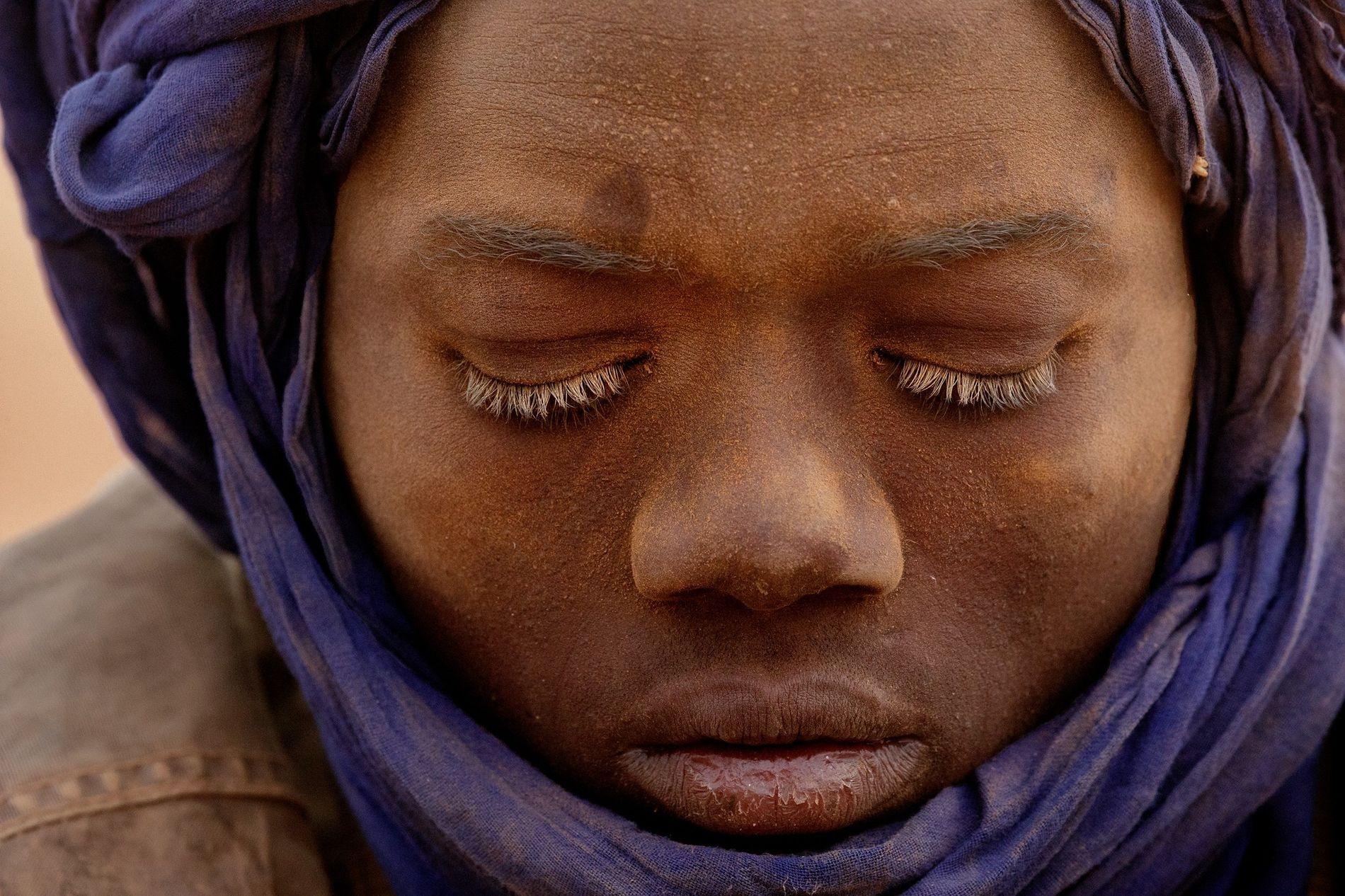 Um adolescente empoeirado por ter estado a trabalhar numa mina. É um dos muitos nigerianos que ...