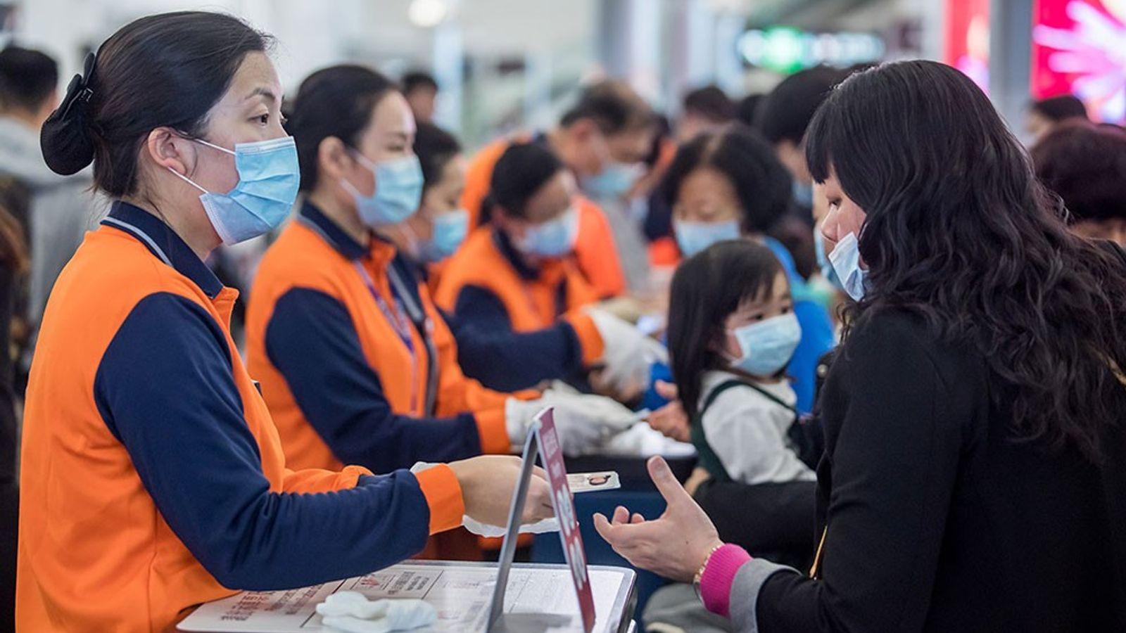 Os trabalhadores ferroviários de Hong Kong, com coletes cor de laranja e máscaras faciais, verificam as ...