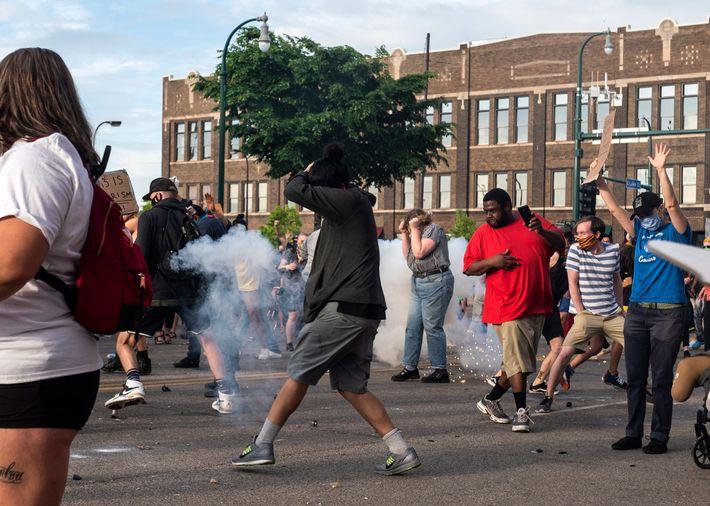 Manifestantes reagem quando uma granada de atordoamento lançada pela polícia explode no meio da multidão, junto ...