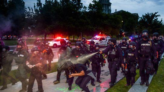 Perto do Capitólio do Estado do Colorado, polícias pulverizam uma mulher com gás pimenta, enquanto os ...