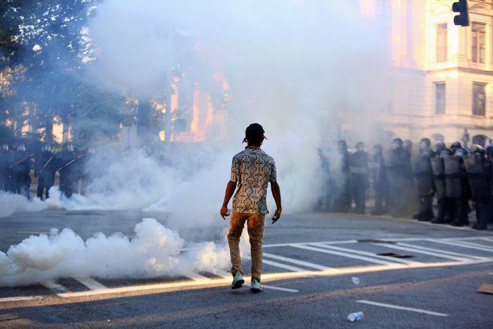Um manifestante no meio de gás lacrimogéneo durante um protesto em Atlanta contra a morte de ...