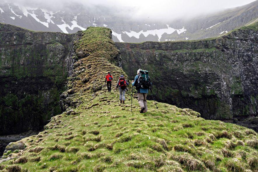 Caminhantes atravessam uma elevação montanhosa, coberta por musgo, na Reserva Natural de Hornstrandir, na Islândia. A ...