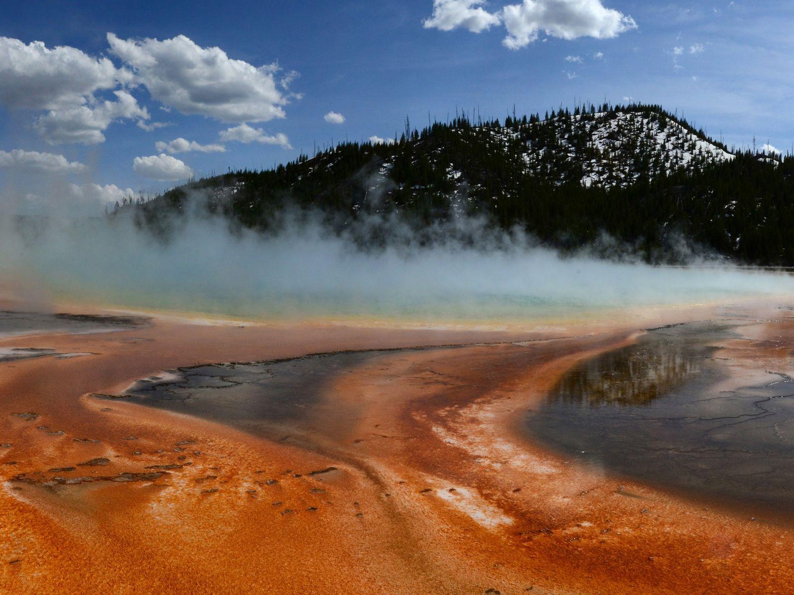 Esteiras viscosas de micróbios alaranjados crescem na Grande Fonte Prismática do Parque Nacional de Yellowstone.