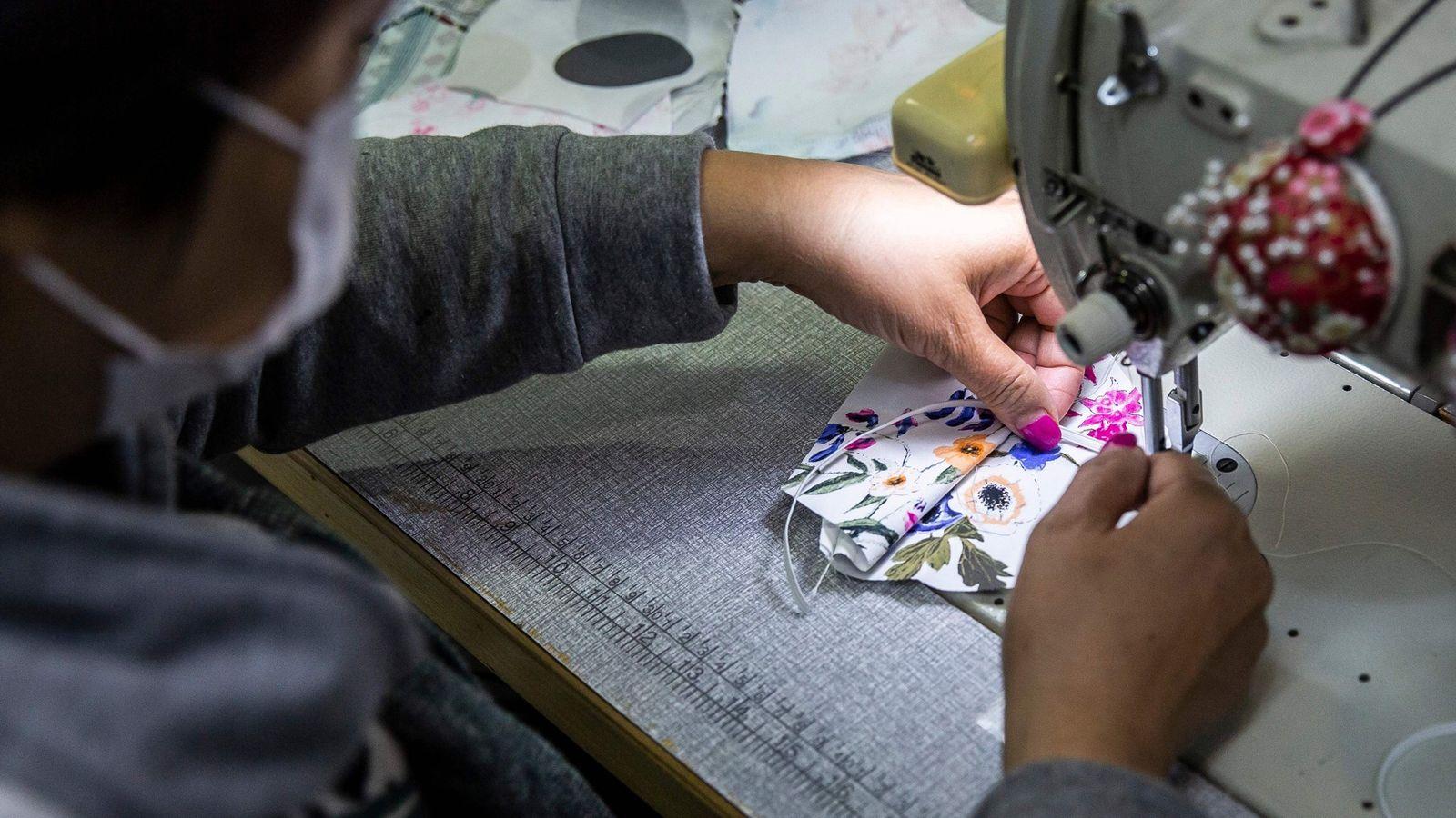 Nesta imagem vemos a costureira Elase Wong a fazer máscaras de material estampado numa loja em ...