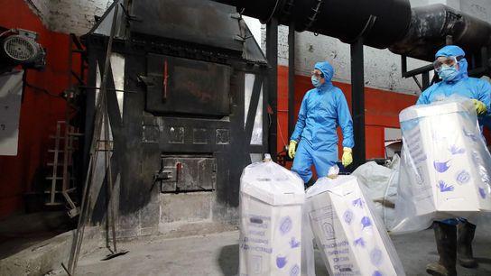 Trabalhadores em Kiev, na Ucrânia, descartam máscaras e luvas médicas usadas, queimando-as num incinerador.