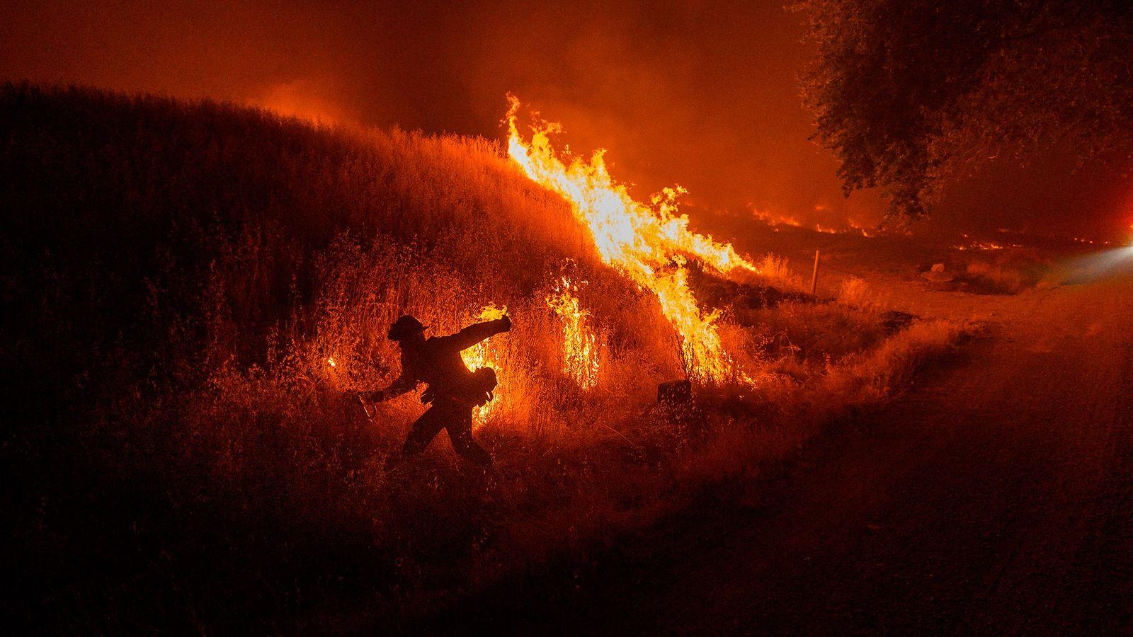 No início de junho, um bombeiro ateava um contrafogo para impedir a propagação do incêndio Quail ...
