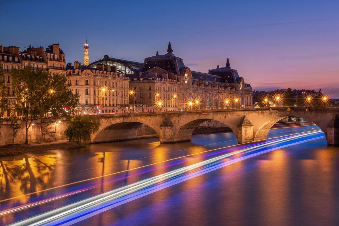 Uma Torre Eiffel iluminada a espreitar atrás do Musée d'Orsay, enquanto os barcos deslizam por baixo ...