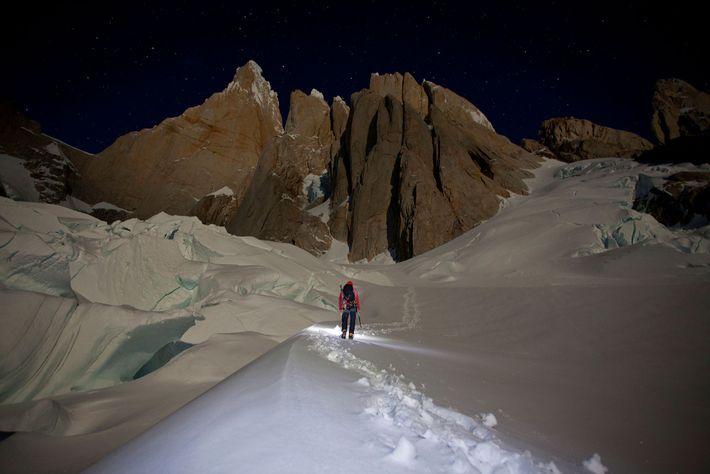 Montanhista faz incidir a luz sobre um cume coberto de neve