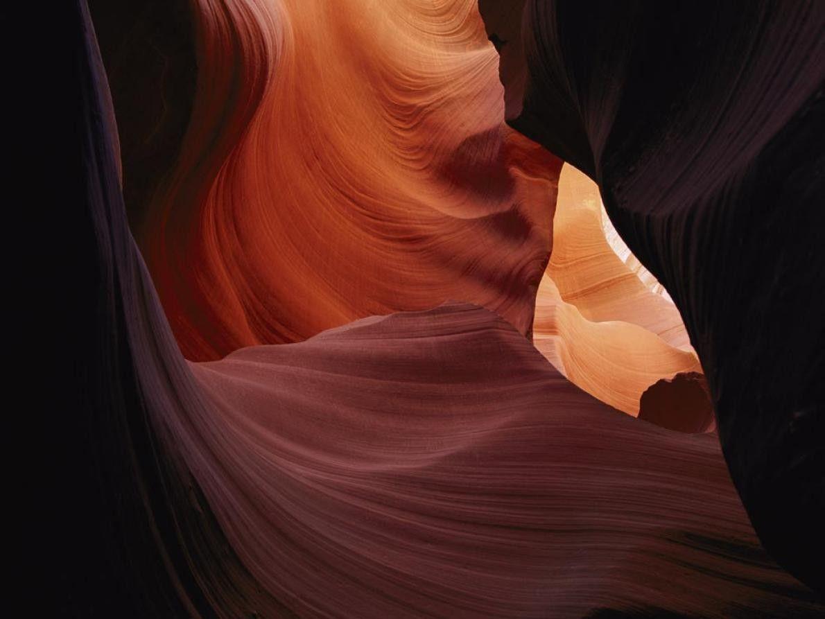 A luz do sol entra pelas fendas do desfiladeiro Antelope no Arizona, pintando as ondulações esculpidas ...