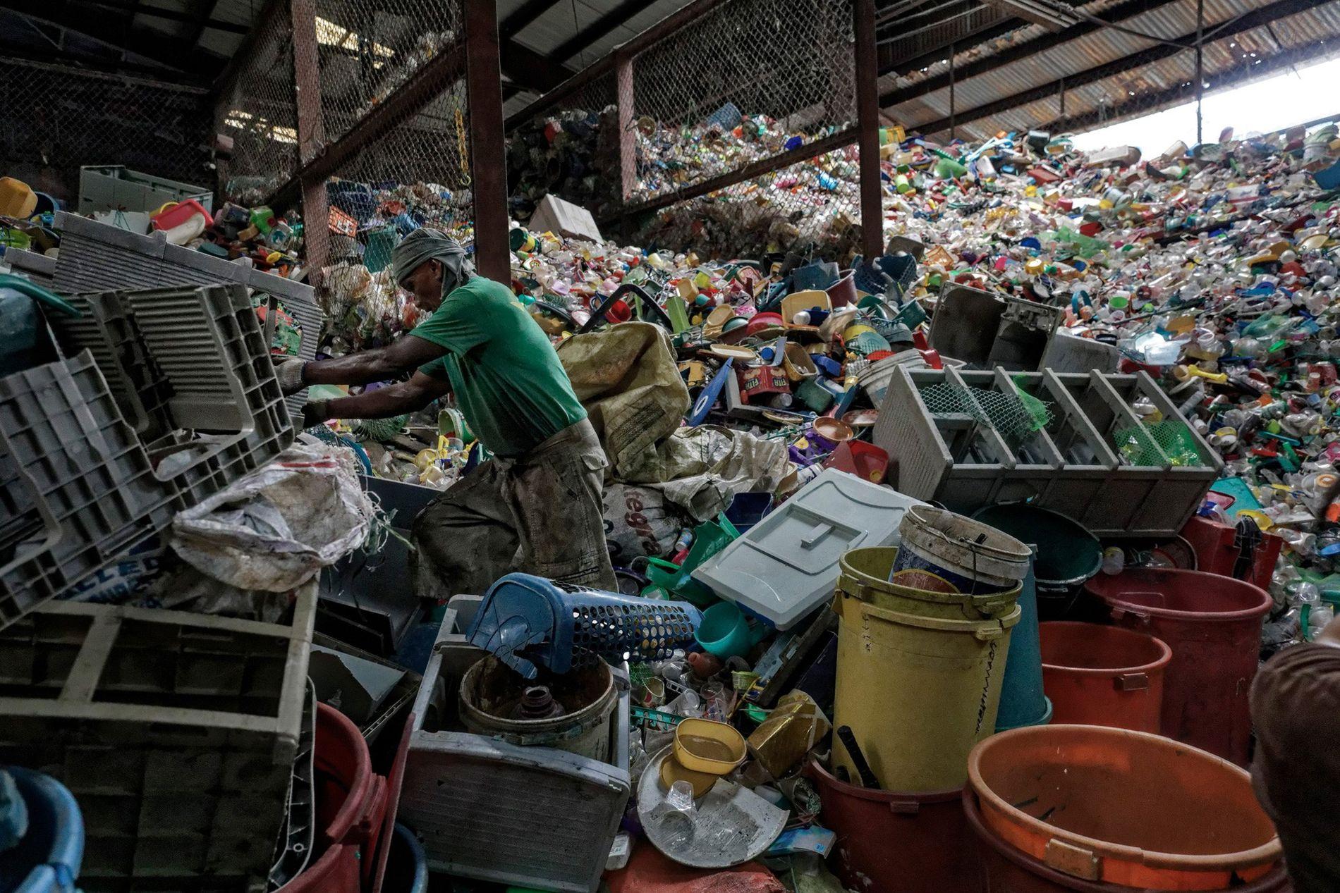 Homem a vasculhar plásticos num armazém