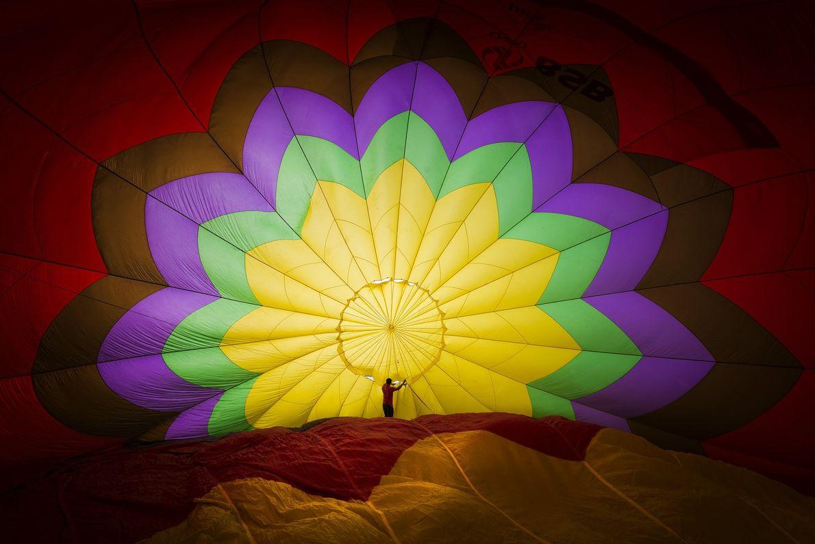 Fotografia de um homem dentro de um balão de ar quente por encher, no Vietname.