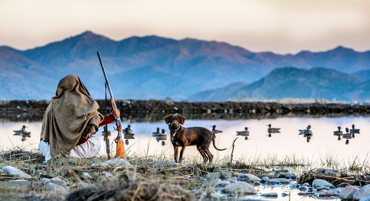 Fotografia de um caçador tribal e do seu cão enquanto aguardam perto de um rio repleto ...