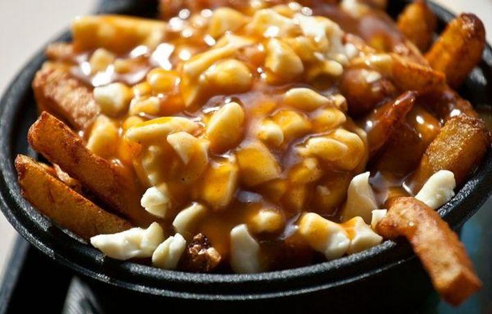 Poutine, um prato de batatas fritas, molho e queijo coalhado, é popular através do Québec