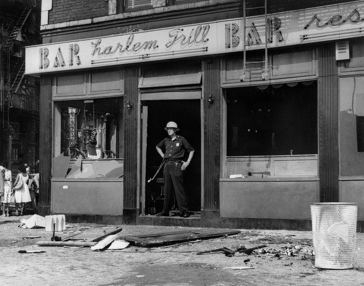 Um polícia bloqueia a porta de um bar destruído durante a revolta no bairro de Harlem, ...