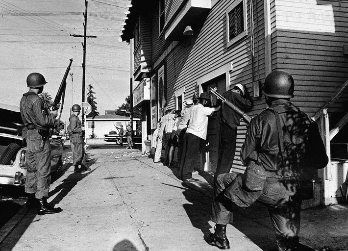 A Guarda Nacional alinhou homens negros contra um edifício em Watts, um bairro de Los Angeles, ...