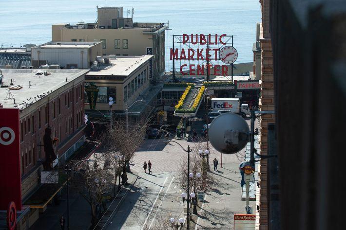 Pessoas a caminhar pelas ruas desertas perto do Public Market Center, em Seattle, no estado de ...